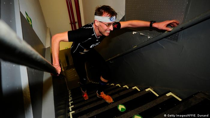 Thomas Dold runs up the stairs in the narrow stairwell of the Empire State Building.