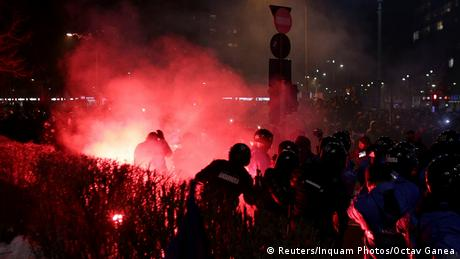 A flare throw by protesters lands near Romanian police
