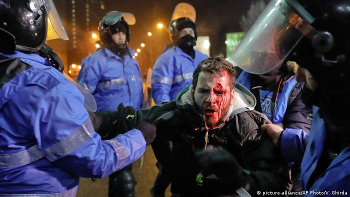 Riot police detain a man after clashes during a protest in Bucharest in February