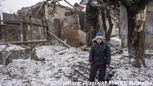 Olexiy, an 8-year-old boy, stands in a crater in front of his house damaged by shelling in the early morning in Avdiivka, eastern Ukraine, Thursday, Feb. 2, 2017. Two Ukrainian soldiers have been killed in the country's industrial east as both government forces and rebels reported shelling on their positions overnight, Ukraine's government said early Thursday. (AP Photo/Evgeniy Maloletka)  