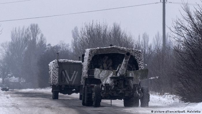 A Ukrainian truck transporting a howitzer drives down a road in eastern Ukraine