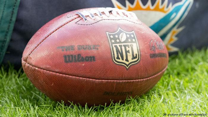 An NFL football with near a Miami Dolphins bag