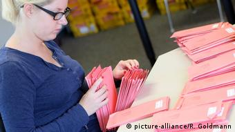 A woman counting mail-in ballots