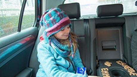 Emma sitzt auf der Rückbank im Auto und legt mit Buchstabenkeksen verschiedene Wörter (DW)