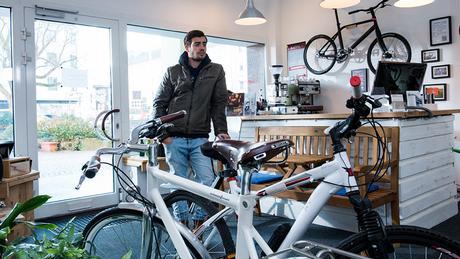 Ein junger Mann steht in einem Fahrradladen.