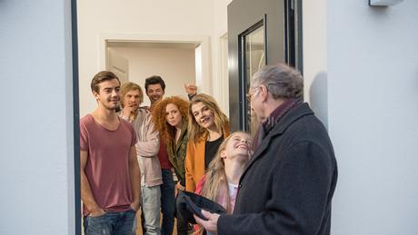 Eine Personengruppe unterhält sich an der Haustür.