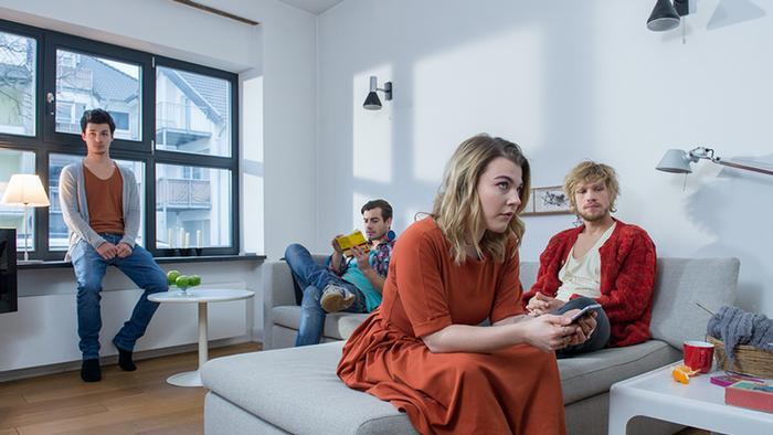 Vier junge Menschen sitzen im Wohnzimmer ihrer WG (DW).