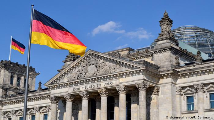 Germany's Reichstag on a sunny day, flags flying out front (picture-alliance/R. Goldmann)