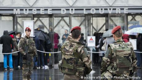 Soldiers stand guard outside the Louvre and point to the building (picture-alliance/AP Photo/K. Zihnioglu)