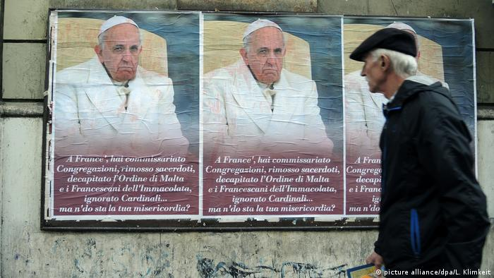 A man looks at posters criticizing the pope