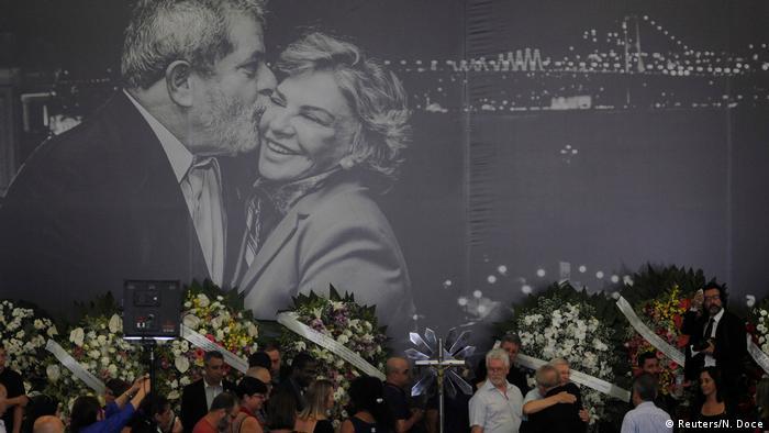 Foto do velório de Marisa. Ao fundo, um grande painel em preto e branco com uma foto de Lula beijando Marisa. À frente, coroas de flores e pessoas abraçando Lula.