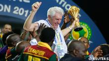Cameroon coach Hugo Broos celebrates with the trophy and teammates after winning the African Cup of Nations