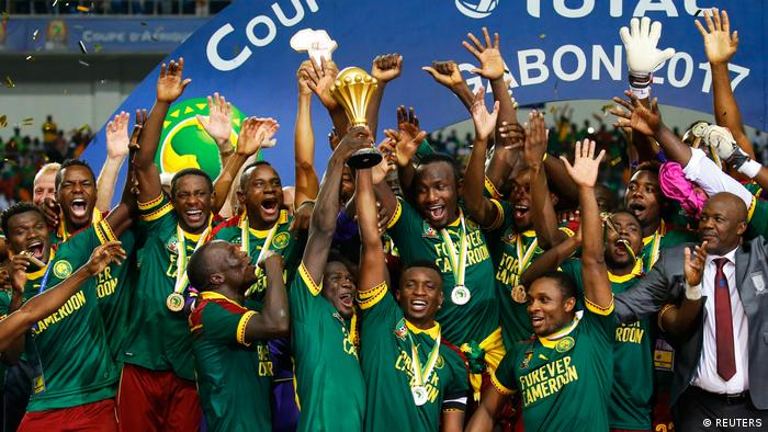 Cameroon's Benjamin Moukandjo celebrates with the trophy and teammates after winning the African Cup of Nations