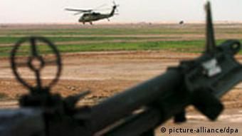 Seen from behind the iron sights of a .50 caliber machine gun mounted in the crew window of a UH60 Blackhawk, another UH60 Blackhawk flies low on the horizon 16 March 2005, over a farming community in the Dhi Qar Province of Southern Iraq.