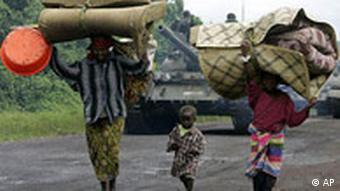 A family with small child walk down a dirt road with their belongings on their heads and a tank behind them