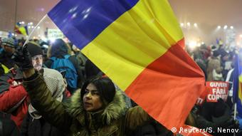 A woman waves a Romanian flag during a protest against the government in Bucharest, February 6