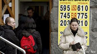 Ukrainians queue at a currency exchange bureau