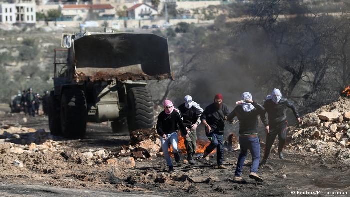 Молодые палестинцы в масках убегают от бульдозера в дыму горящего мусора