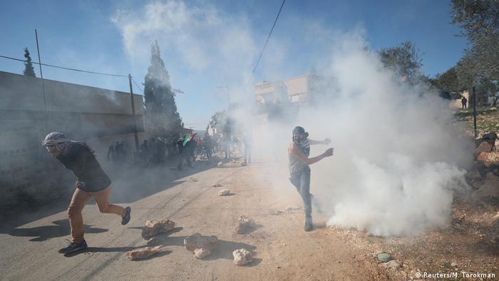 Палестинцы в масках бегут в дыму по дороге, под ногами у них валяются камни