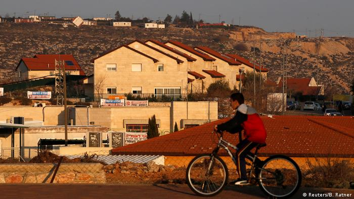Юный поселенец едет на велосипеде мимо ряда домов