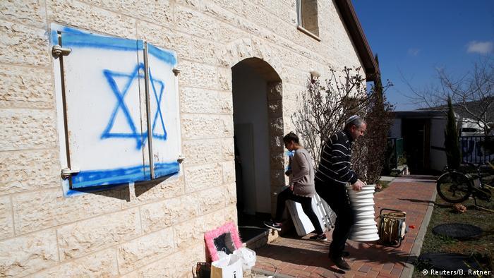 Мужчина и женщина выносят вещи из здания в поселении Офра