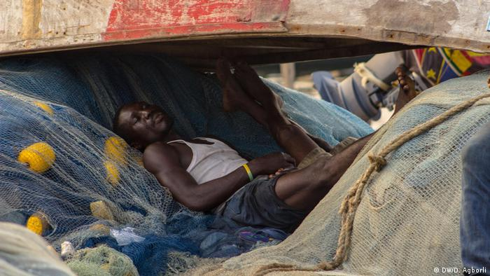 A fisherman in Ghana takes a nap under a wooden boat. (DW/D. Agborli)