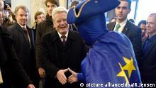 Bundespräsident Joachim Gauck wird am 07.02.2017 von einem in eine Europa-Fahne gehüllten Darsteller im Filmtheater Lumiere bei einem Fest zum Thema 25 Jahre Maastrichter Verträge in Maastricht (Niederlande) begrüßt. Foto: Rainer Jensen/dpa +++(c) dpa - Bildfunk+++   Verwendung weltweit