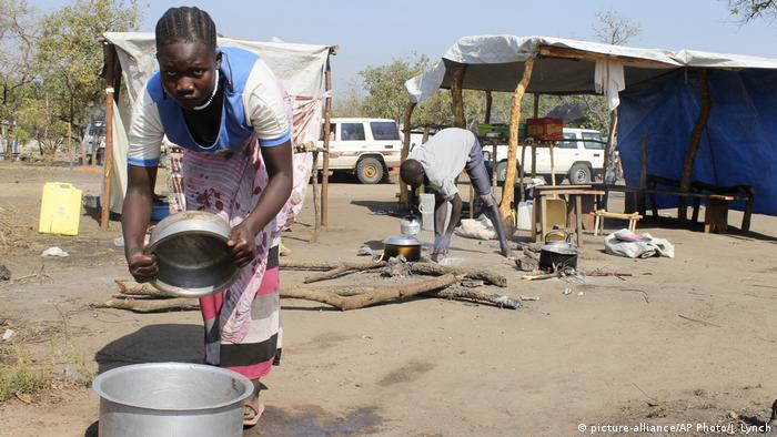 A woman in a refugee camp cooking food out in the open (picture-alliance/AP Photo/J. Lynch)