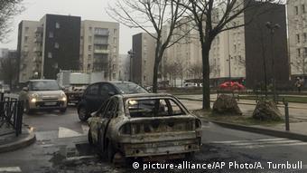 Сожженный автомобиль в результате беспорядков в Оне-су-Буа