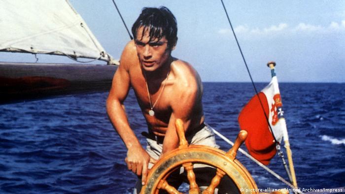 Filmstill von Plein Soleil - Nur die Sonne war Zeuge mit Alain Delon am Steuerrad eines Segelschiffs auf dem Meer.