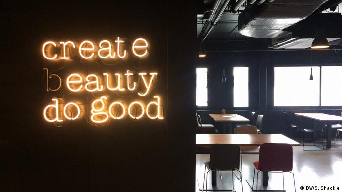 The company's motto - Create beauty, do good - is displayed in the lobby.