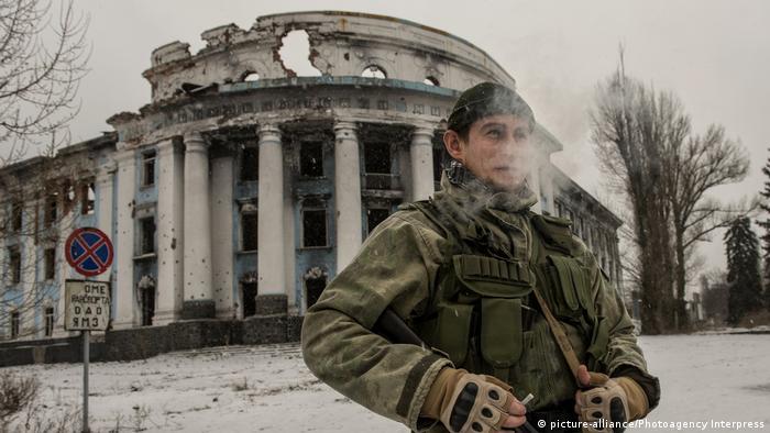 Вооруженный сепаратист в Донецке на фоне поврежденного здания