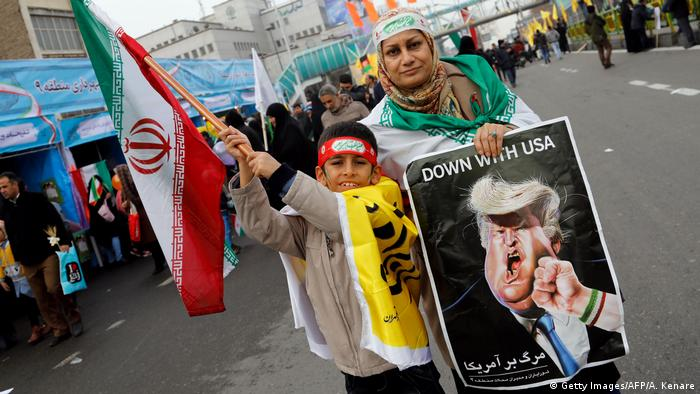 An Iranian woman holds a placard showing a caricature of US President Donald Trump (Getty Images/AFP/A. Kenare)