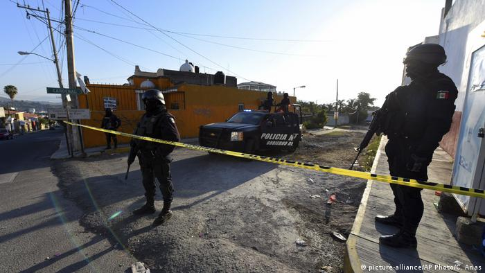 Mexican police guard an area following a gun battle between cartels and federal authorities (AP Photo/Chris Arias)