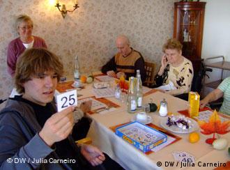 Young man playing a game with several seniors in a retirement home
