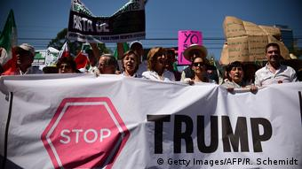 People hold signs during an anti-Trump march in Mexico City on February 12, 2017