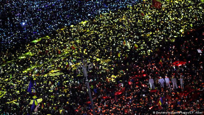 Гигантский румынский флаг, изображенный с помощью огней тысяч смартфонов, которые подсвечивают красные, синие и желтые полоски бумаги