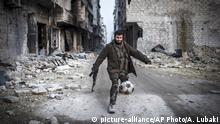 A Syrian rebel plays football in the Saif al-Dawlah neighborhood of Aleppo, Syria, Wednesday, Jan. 2, 2013. The United Nations estimated Wednesday that more than 60,000 people have been killed in Syria's 21-month-old uprising against authoritarian rule, a toll one-third higher than what anti-regime activists had counted. The U.N. human rights chief called the toll truly shocking. (AP Photo/Andoni Lubacki) |