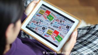 Женщина держит планшет с логотипами разных партий на экране