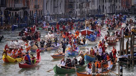 Παντού στην πόλη ο κόσμος γλεντά. Ακόμη και τα γραφικά κανάλια της Βενετίας γεμίζουν χρώμα και κίνηση, όπου εκατοντάδες μεταμφιεσμένοι παρελαύνουν όρθιοι επάνω σε γόνδολες.