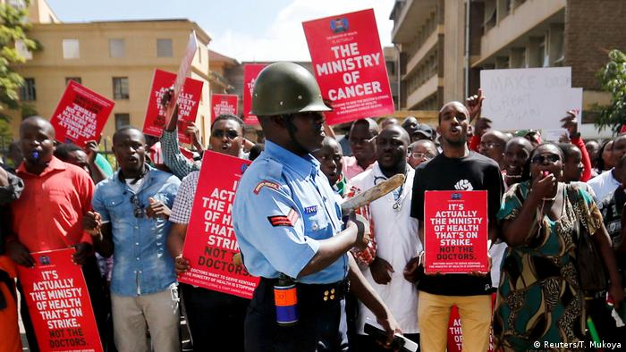 A riot policeman stands guard as doctors chant slogans after their case to demand fulfilment of a 2013 agreement between their union and the government was heard employment and labour relations courts in Nairobi, Kenya (Reuters/T. Mukoya)