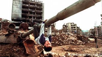 Ο μικρός Κενάν παίζει κρεμασμένος από τη κάνη ενός ρωσικού τανκς. Εικόνα καθημερινής ζωής το 1996 λίγο έξω απο το Σαράγεβο