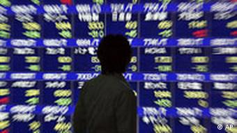A passer-by looks at an electronic stock board in downtown Tokyo