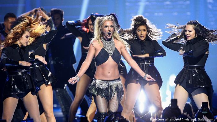 Britney Spears performing on stage with many other dancers.