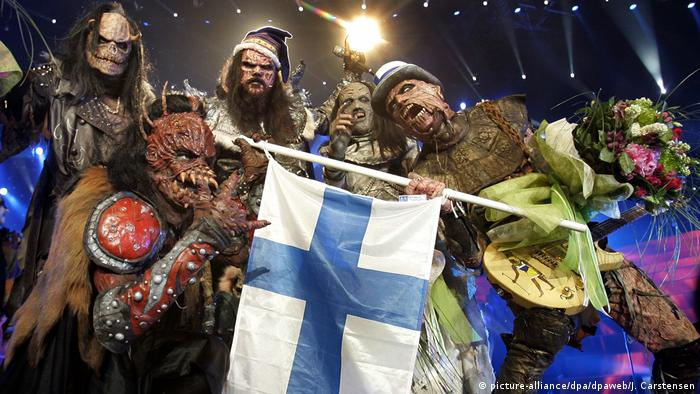 five men wearing horror masks holding a Finnish flag (picture-alliance/dpa/dpaweb/J. Carstensen)