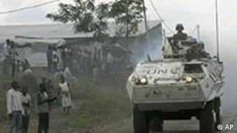 People look on as United Nations armoured vehicles patrol in Goma