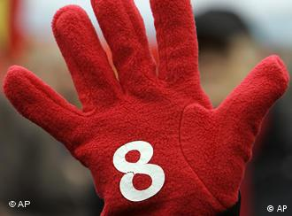 A striker's hand covered in a red glove with a white 8 on it