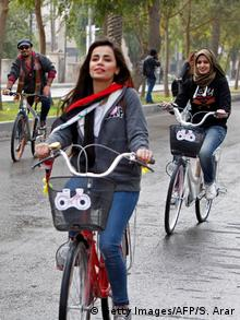 Iraqi female activists ride bikes during a protest
