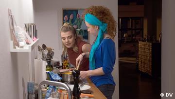 Nina and Lisa standing at the kitchen table, Nina stirring a pot, Lisa watching