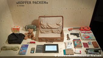 Ein geöffneter, leerer Koffer mit verschiedenen Gegenständen rundherum